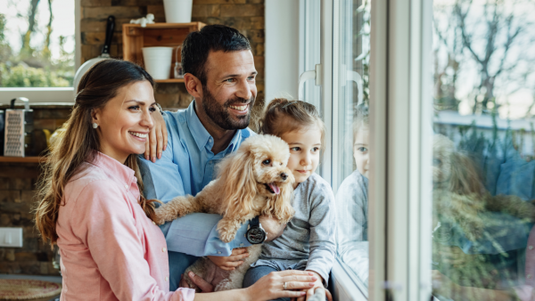 Happy Family of Three with Dog in Front of the Window