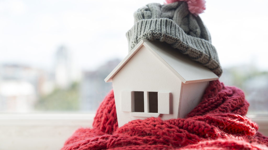 Hand Holds Miniature House dressed in a Hat and Scarf