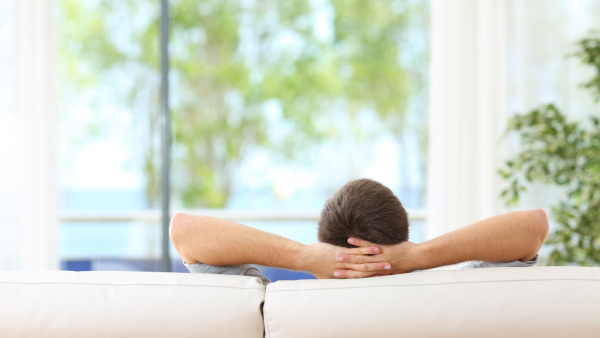 Man Sitting Calm on Sofa In Front Of Minimal Aluminum System