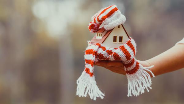 Χέρι κρατάει Σπίτι σε Μικρογραφία ντυμένο με Σκούφο και Κασκόλ